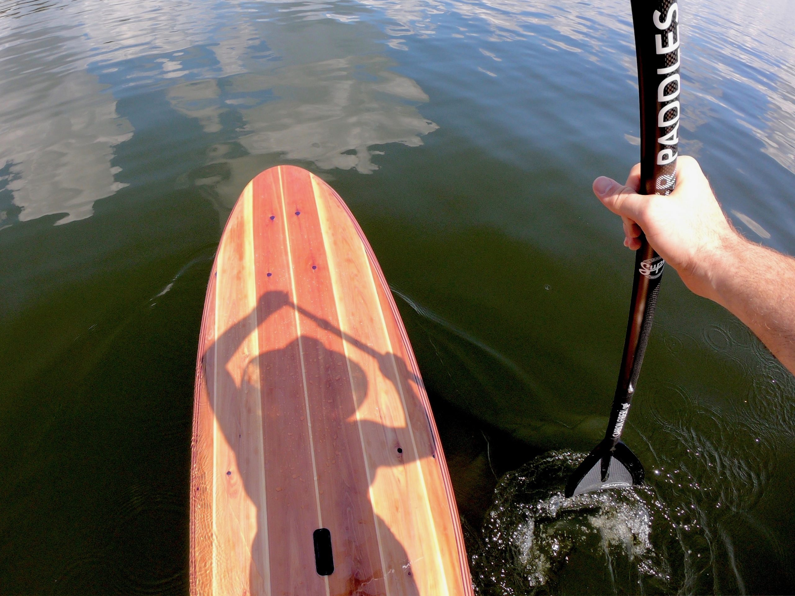 wood SUP being paddled